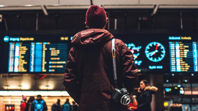 Man standing in front of airport departure board